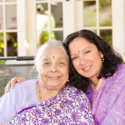Two generations of an Asian Indian family, senior mother and adult daughter dressed in traditional saris for a family outdoor portrait.