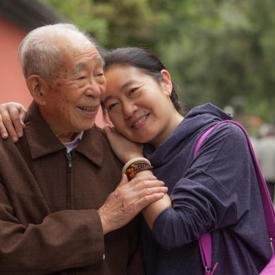 90 year old Chines man sharing a tender moment with his adult daughter